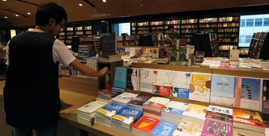 A salesclerk arranges books at Eslite bookstore before its opening in Hong Kong August 10, 2012. Taiwanese bookstore Eslite, one of the largest retail bookstore chains in Taiwan, opened their first overseas store on Friday. The three-storey-high shop, which stretches to 41,000 square feet, is the city's largest bookstore. REUTERS/Tyrone Siu (CHINA - Tags: SOCIETY BUSINESS)