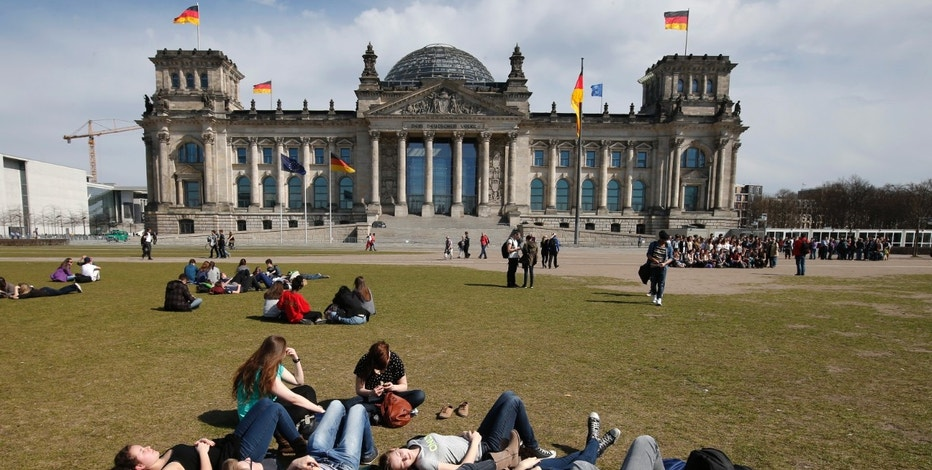 People enjoy the sun on a patch of grass in front of the Reichstags building in Berlin, April 15, 2013.        REUTERS/Fabrizio Bensch (GERMANY - Tags: SOCIETY ENVIRONMENT) - RTXYMKB