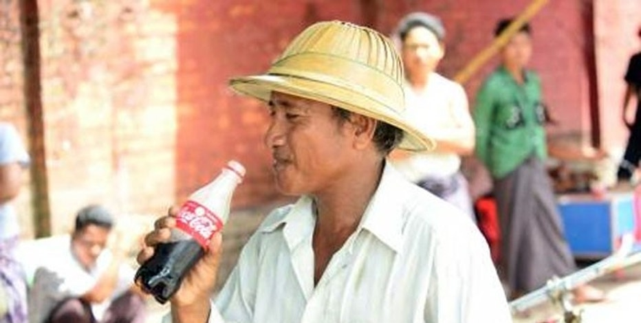 A Myanmar citizen enjoying a Coca-Cola produced in the country for the first time in more than 60 years.