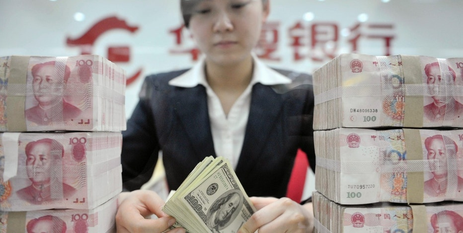 An employee counts U.S. dollar banknotes at a branch of Huaxia Bank in Shenyang, Liaoning province March 18, 2010. A rise in the yuan would be a disaster for labour-intensive Chinese exporters, a semi-official trade group said on Thursday, as frictions grow with the U.S. and other Western powers over Beijing's stable currency policy. The China Council for the Promotion of International Trade was checking with more than 1,000 exporters in 12 industries on whether they could cope with a stronger exchange rate, Zhang Wei, vice-chairman of the association, said. REUTERS/Sheng Li (CHINA - Tags: BUSINESS POLITICS)