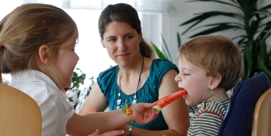 Claudia (C) eats fruits with her children Michael (R) and Katharina at home in Durach, southern Germany June 20, 2012. German Chancellor Angela Merkel is looking to establish a childcare allowance for stay-at-home mothers. The draft law, known as Betreuungsgeld, will provide mothers who stay at home with their children, about 150 Euros ($190) per month. REUTERS/Michaela Rehle (GERMANY - Tags: EDUCATION POLITICS SOCIETY)