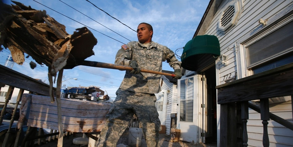U.S. Army Specialist  Bryson Vea from the 10th Mountain Division based at Fort Drum, New York volunteers on Veterans Day to clear debris from homes destroyed by Hurricane Sandy, on Staten Island in New York City, November 12, 2012. Police raised the storm-related fatality toll in New York City to 43 and at least 121 people have perished in the storm, which caused an estimated $50 billion in property damage and economic losses and ranks as one of the most destructive natural disasters to hit the U.S. Northeast. REUTERS/Mike Segar (UNITED STATES - Tags: ENVIRONMENT DISASTER MILITARY) - RTR3ABWY