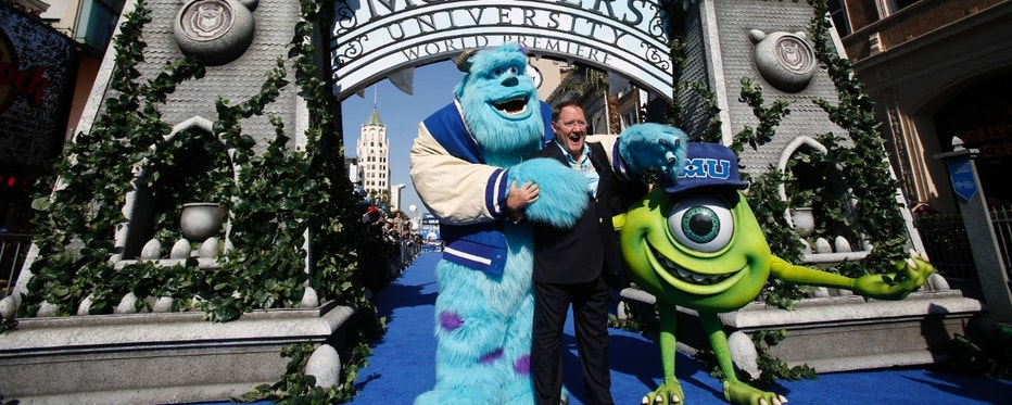 "John Lasseter (C), Chief Creative Officer at Pixar and Walt Disney animation studios, poses with life-size characters of Mike (R) and Sullivan at the premiere of the film ""Monsters University"" at El Capitan theatre in Hollywood, California June 17, 2013. The movie opens in the U.S. on June 21.   REUTERS/Mario Anzuoni (UNITED STATES - Tags: ENTERTAINMENT BUSINESS) - RTX10RMG"