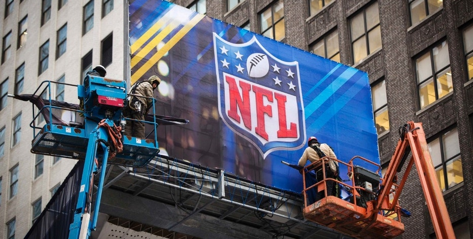Workers hang signage on a booth on Broadway as preparations continue for Super Bowl XLVIII in New York January 28, 2014.  New Jersey's MetLife Stadium will host the first outdoor, cold-weather Super Bowl February 2. As part of festivities, the NFL is sponsoring activities along 'Super Bowl Boulevard', located on Broadway between 34th and 47th streets in Manhattan.   REUTERS/Lucas Jackson (UNITED STATES - Tags: SPORT SOCIETY FOOTBALL)