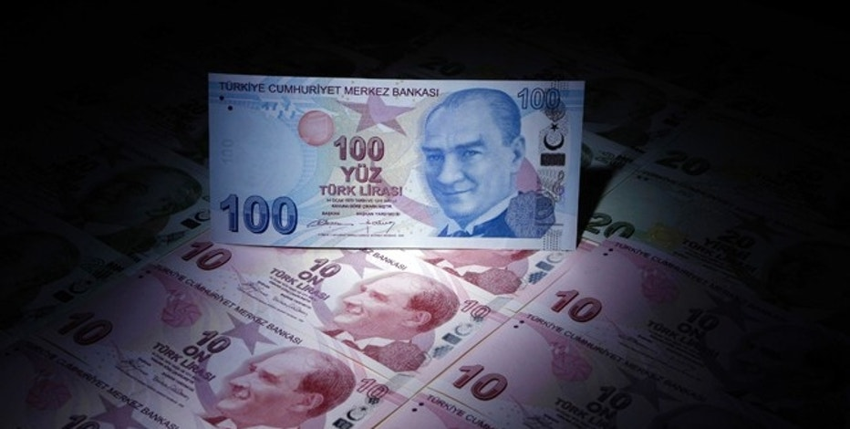 A Turkish 100 lira banknote is seen on top of 10 lira banknotes in this illustration picture taken in Istanbul January 28, 2014. Turkey's central bank governor raises hopes of emergency rate hike in face of opposition from Prime Minister Tayyip Erdogan, denying he is hostage to political pressures and vowing to fight rising inflation and tumbling lira. REUTERS/Murad Sezer (TURKEY - Tags: BUSINESS POLITICS TPX IMAGES OF THE DAY)