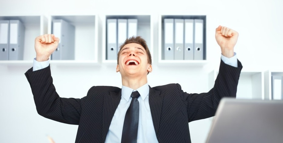 Young businessman celebrating his success with arms raised at his workplace in bright office