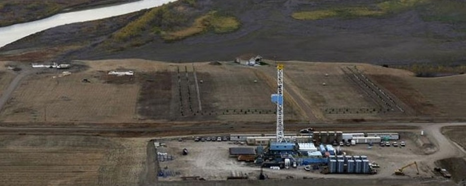 An oil drilling rig operates near homes, farm fields and the Missouri River outside Williston, North Dakota, October 19, 2012. Thousands of people have flooded into North Dakota to work in state's oil drilling boom.