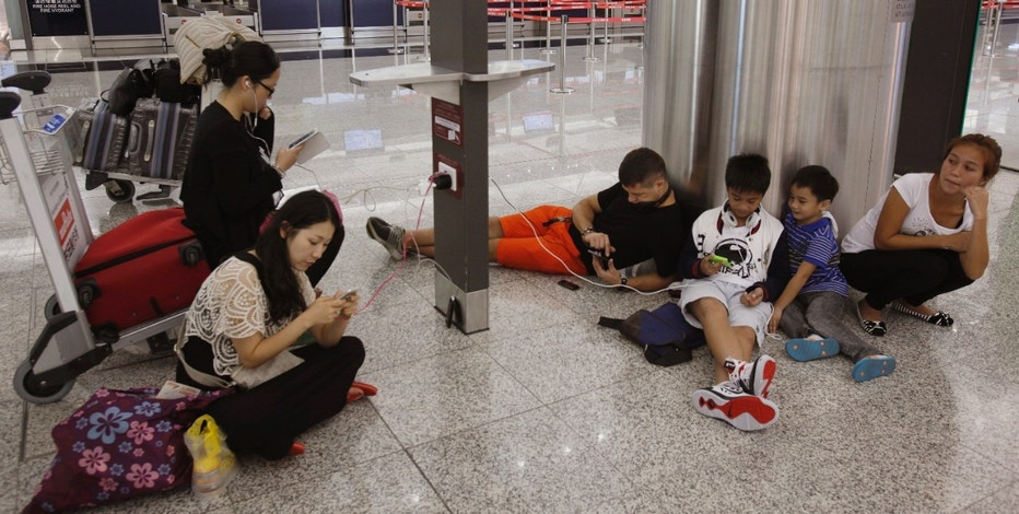 Passengers from South Korea (L), the Philippines (R) and Poland (4th R), whose flights to their home countries are cancelled in anticipation of typhoon Usagi, charge their tablet and smartphones at Hong Kong International Airport September 22, 2013. Hong Kong was bracing on Sunday for this year's most powerful typhoon, with government meteorologists warning of severe flooding created by a double whammy of powerful winds and exceptionally high tides. Typhoon Usagi, the strongest storm to hit the Western Pacific this year, is expected to hit the Asian financial centre late on Sunday and early on Monday. REUTERS/Bobby Yip (CHINA - Tags: ENVIRONMENT TRANSPORT) - RTX13UGE