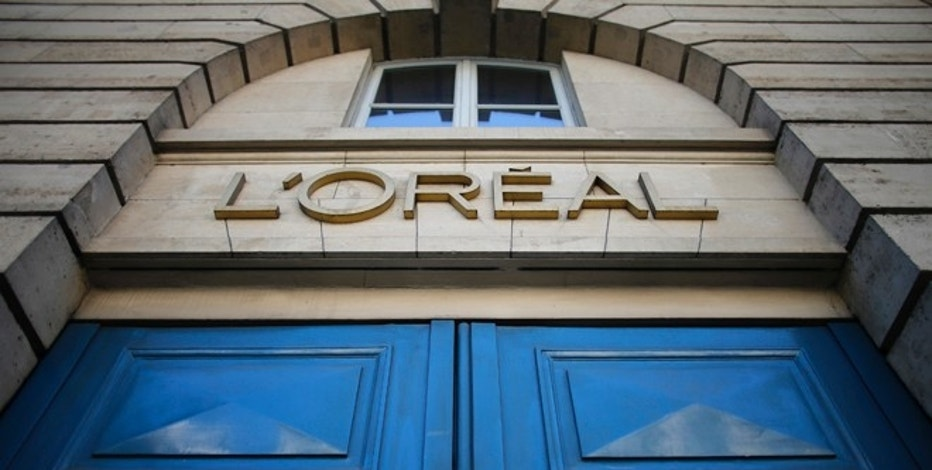 A logo is seen over the entrance of Cosmetics company L'Oreal building in Paris, August 16, 2013. L'Oreal SA has offered to buy Chinese facial mask maker Magic Holdings International Ltd, a move that would put the world's largest cosmetics group in the lead of the fastest growing sector in China's $15 billion skincare market.   REUTERS/Christian Hartmann (FRANCE - Tags: BUSINESS) - RTX12NGG