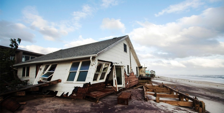 A damaged house is seen after Hurricane Sandy passed through in the greatly affected community of Atlantique on Fire Island, New York October 30, 2012. Millions of people were left reeling in the aftermath of the whipping winds and heavy rains of the massive storm Sandy on Tuesday as New York City and many parts of the eastern U.S. struggled with epic flooding and extensive power outages.      REUTERS/Lucas Jackson (UNITED STATES - Tags: ENVIRONMENT DISASTER)