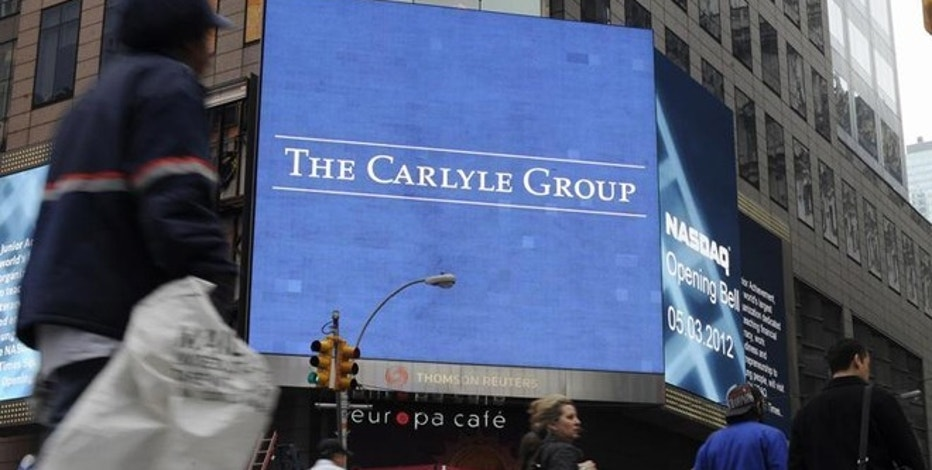 Passersby walk in front of video monitors announcing the Carlyle Group's listing on the NASDAQ market site in New York's Times Square after the opening bell for trading, May 3, 2012. REUTERS/Keith Bedford