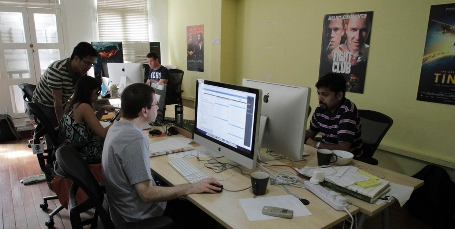 Staff members work on their computers at Viki's office in Singapore May 24, 2012. Who would want to watch a South Korean soap that was a flop back home? Lots of people, it turns out - something that Singapore-based startup Viki feels vindicates its business model: an ad-supported streaming TV and movie site where unpaid fans add the foreign subtitles. The service plays on a number of trends both in Asia and worldwide: a passion for watching video over the Internet; a growing interest in content from other countries; and the emergence of more sophisticated software to spread the burden of laborious tasks like subtitling. REUTERS/Tim Chong (SINGAPORE - Tags: BUSINESS SCIENCE TECHNOLOGY)
