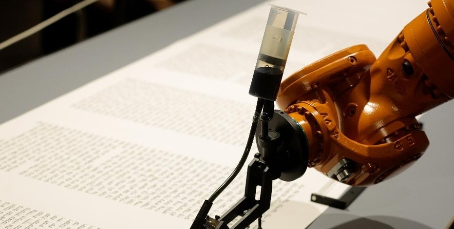 A robot writes a Torah at an installation in the Jewish Museum in Berlin, Germany, Thursday, July 10, 2014. It is an installation by the artist group robotolab. The robot is equipped with a pen nib and ink and will write the Torah in human speed. (AP Photo/Markus Schreiber)