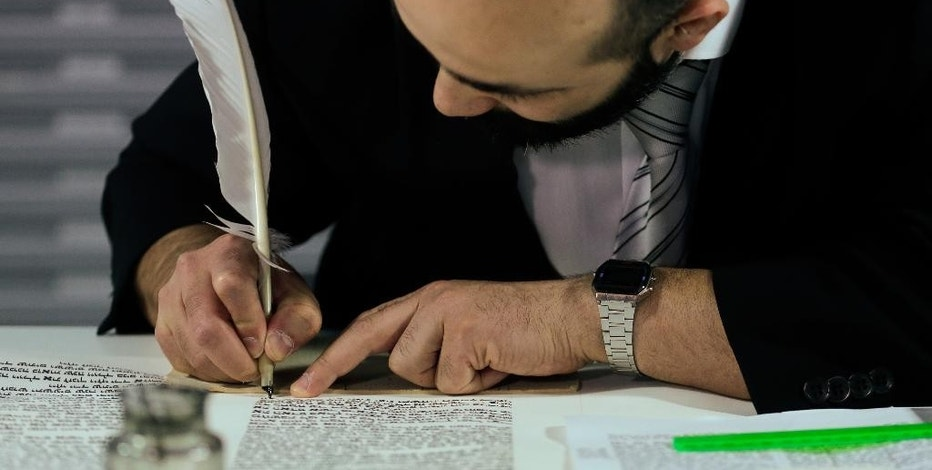Rabbi Reuven Yaacobov shows how to write a Torah by hand at an exhibition in the Jewish Museum in Berlin, Germany, Thursday, July 10, 2014. (AP Photo/Markus Schreiber)