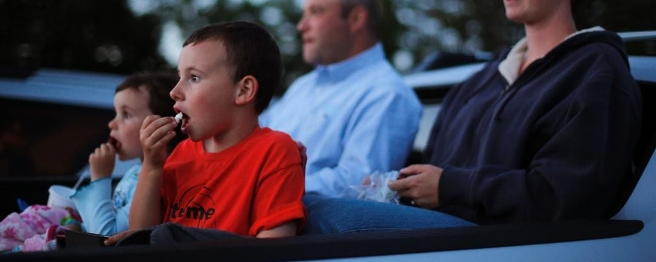 In this photo made Thursday, June 26, 2014, Mike and Naomi Gibel, and their children Norah, 4, left, and Issak, 7, watch a movie from the back of a pick-up truck at the Saco Drive-In in Saco, Maine.   Many in the movie industry feared the need to convert to digital could be the death knell for drive-ins, but drive-in operators are finding creative ways to afford the switch.  Drive-in movie theater operators say more than 200 of the remaining 348 drive-ins in the country have made the expensive conversion from film to digital, which typically costs more than $70,000. (AP Photo/Robert F. Bukaty)