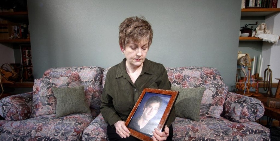 FILE – In this Monday, Feb. 27, 2012 file photo, Karen Williams, who sued Facebook for access to her 22-year-old son Loren's account after he died in a 2005 motorcycle accident, looks at a portrait of her son at her home in Beaverton, Ore. The Uniform Law Commission on Wednesday, July 16, 2014 was expected to endorse a plan to automatically give loved ones access to — but not control of — all digital accounts, unless otherwise specified.  (AP Photo/Rick Bowmer, File)