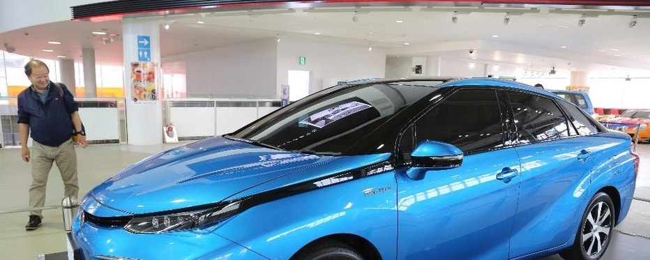 In this June 26, 2014 photo, a visitor looks at Toyota Motor's new fuel cell vehicle (FCV) on display at the company's showroom in Tokyo. Buoyed by its success with electric-gasoline hybrid vehicles, Toyota is betting that drivers will embrace hydrogen fuel cells, an even cleaner technology that runs on the energy created by an electrochemical reaction when oxygen in the air combines with hydrogen stored as fuel. (AP Photo/Koji Sasahara)