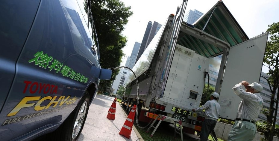 In this July 14, 2014 photo, a Toyota fuel cell hybrid vehicle is refueled from a mobile hydrogen station at the Ministery of Economy, Trade and Industry in Tokyo.  Toyota's still-to-be-officially-named vehicle goes on sale in Japan sometime before April 2015, and within a half year after that in the U.S. and Europe.  Apart from cost, the other big drawback is lack of hydrogen fueling stations. Only about 30 of them exist throughout Japan so far, although the government is leading a push to get more built in coming months. Lack of charging stations is also a weakness for electric cars but there are fewer obstacles to establishing and supplying that infrastructure because electricity networks are already in place. (AP Photo/Eugene Hoshiko)