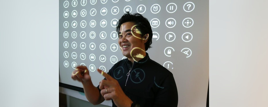 """In this photo taken July 3, 2014, Albert Shum, who heads interaction design across a range of Microsoft products including personal computer operating systems, Xbox game consoles, and phones, poses for a photo in front of a projection of icons used by those systems, in Redmond, Wash. A former designer for shoemaker Nike, Shum was part of the team that revolutionized the Windows Phone design to feature the boxy, so-called """"live tiles"""" that are central to the touch-based interface in Windows 8. (AP Photo/Ted S. Warren)"""