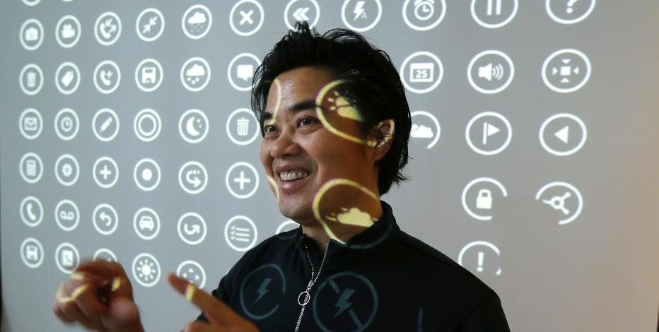 "In this photo taken July 3, 2014, Albert Shum, who heads interaction design across a range of Microsoft products including personal computer operating systems, Xbox game consoles, and phones, poses for a photo in front of a projection of icons used by those systems, in Redmond, Wash. A former designer for shoemaker Nike, Shum was part of the team that revolutionized the Windows Phone design to feature the boxy, so-called ""live tiles"" that are central to the touch-based interface in Windows 8. (AP Photo/Ted S. Warren)"