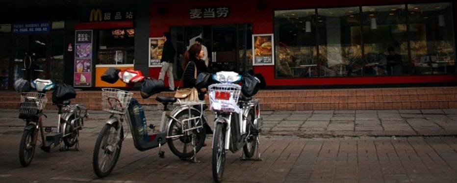 A woman walks past electric bikes sitting outside a McDonalds fast-food outlet in central Beijing March 20, 2012. China's State Food and Drug Administration