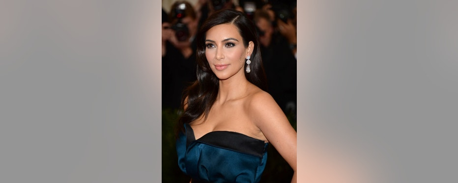 """FILE - In this May 5, 2014, file photo, Kim Kardashian attends The Metropolitan Museum of Art's Costume Institute benefit gala celebrating """"Charles James: Beyond Fashion"""" in New York. The Environmental Protection Agency's fight to clean up water pollution is getting a splash of pop culture, thanks to a flub involving Kardashian. The verified Twitter account for the EPA's Office of Water mistakenly published a note on July 21 about an online game, """"Kim Kardashian: Hollywood,"""" in which players walk red carpets, attend photo shoots and get dolled up like a Kardashian. An agency spokeswoman said the off-topic tweet was done by a temporary employee. (Photo by Evan Agostini/Invision/AP)"""