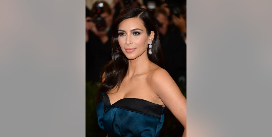 "FILE - In this May 5, 2014, file photo, Kim Kardashian attends The Metropolitan Museum of Art's Costume Institute benefit gala celebrating ""Charles James: Beyond Fashion"" in New York. The Environmental Protection Agency's fight to clean up water pollution is getting a splash of pop culture, thanks to a flub involving Kardashian. The verified Twitter account for the EPA's Office of Water mistakenly published a note on July 21 about an online game, ""Kim Kardashian: Hollywood,"" in which players walk red carpets, attend photo shoots and get dolled up like a Kardashian. An agency spokeswoman said the off-topic tweet was done by a temporary employee. (Photo by Evan Agostini/Invision/AP)"