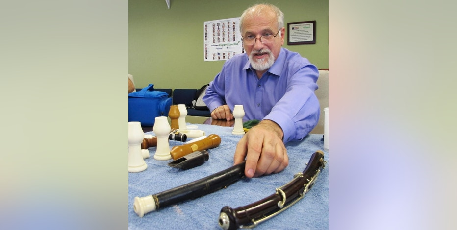 In this July 17, 2014 photo, Dr. Robert Howe, a medical doctor and a PhD candidate in music history, displays antique English horns at the University of Connecticut's Depot Campus in Mansfield, Conn. Howe and his colleagues have been using CT scans and 3D printing to unlock the secrets of antique instruments and make replica parts that will allow them to be played. (AP Photo/Pat Eaton-Robb)