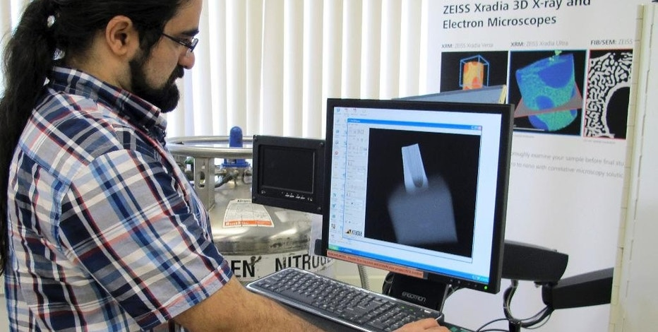 In this July 17, 2014 photo, Sina Shahbazmohamadi, an engineer and the University of Connecticut's director for advanced 3D imaging, looks at a CT scan at UConn's Depot Campus in Mansfield, Conn., showing a mouthpiece for a 19th-century saxophone built by inventor Adolphe Sax. Researchers at the school are using CT scanning and 3D printing to study and reproduce antique musical instruments. (AP Photo/Pat Eaton-Robb)