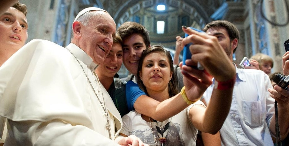 FILE - In this file photo Wednesday, Aug. 28, 2013 Pope Francis has his picture taken inside St. Peter's Basilica with youths from the Italian Diocese of Piacenza and Bobbio who came to Rome for a pilgrimage, at the Vatican. (AP Photo/L'Osservatore Romano, File)