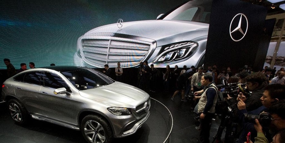 In this photo taken Sunday, April 20, 2014, visitors look at the latest model from Mercedes at an auto show in Beijing, China. Chinese regulators have launched a series of anti-monopoly investigations of foreign automakers and technology providers, stepping up pressure on foreign companies that feel increasingly unwelcome in China. On Wednesday, a regulator said Chrysler and Germany's Audi will be punished for violating anti-monopoly rules. Mercedes Benz and Japanese companies also are under scrutiny. (AP Photo/Ng Han Guan)