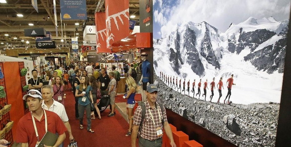 Visitors walk next to a large display at the Outdoor Retailer's summer show in Salt Lake City on Wednesday, Aug. 6, 2014. The biannual show brings thousands to Utah. The world's largest outdoor-gear trade show runs Wednesday through Saturday at the Salt Palace Convention Center. (AP Photo/Rick Bowmer)