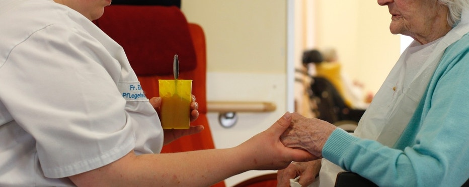 A pensioner receives help from a hospital nurse during lunchtime in a residential home for the elderly in Eichenau near Munich June 21, 2011.  Picture taken June 21.  REUTERS/Michaela Rehle (GERMANY - Tags: HEALTH SOCIETY) FOR EDITORIAL USE ONLY. NOT FOR SALE FOR MARKETING OR ADVERTISING CAMPAIGNS