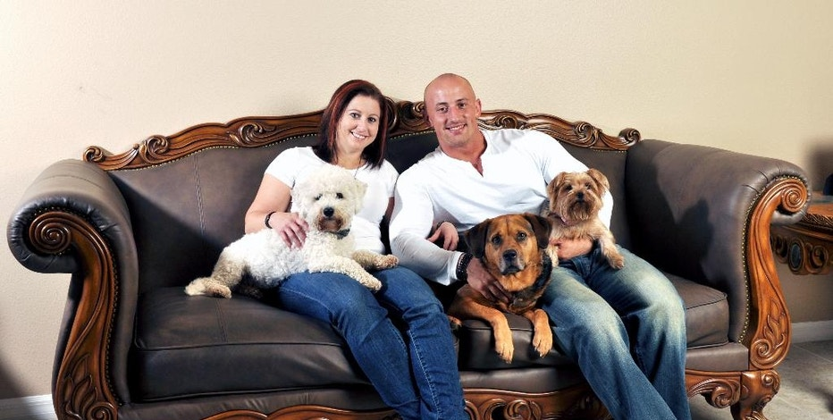 "In this July 2014 photo provided by Kris Rotonda, Rotonda, who founded YouMustLoveDogsDating.com, poses with his girlfriend Denise Fernandez and three of his four dogs, Kobe, a bichon frise, Jordan, a bull mastiff German shepherd and Samoyed mix, and Coco, a Yorkie in Clearwater, Fla. ""Dogs on first dates are amazing icebreakers,"" said Rotonda, who started up the site last year that now has 2 million members. ""You find out right off the bat how everyone in a relationship will fit in."" (AP Photo/Rebecca Brittain)"
