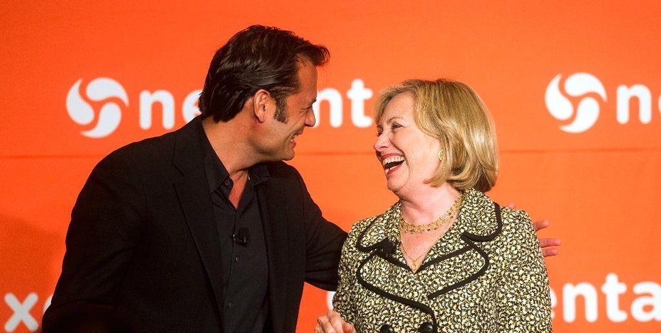 Nexenta CEO Tarkan Maner, left, presents former Secretary of State Hillary Rodham Clinton with a pair of his company's trademark orange sneakers during the Nexenta OpenSDx Summit Thursday, Aug. 28, 2014, in San Francisco. (AP Photo/Noah Berger)