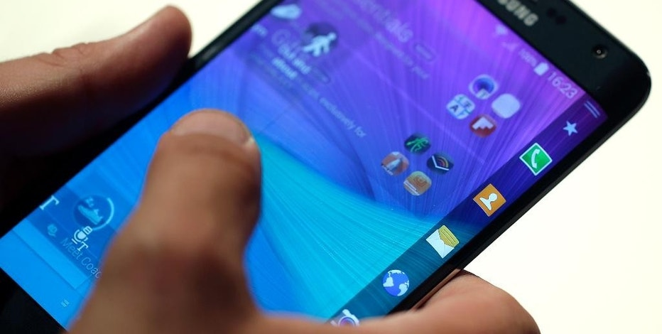 A visitor tabs on the display of a Samsung Galaxy Note edge during an 'Unpacked event' at the IFA, one of the world's largest trade fairs for consumer electronics and electrical home appliances in Berlin, Germany, Wednesday, Sept. 3, 2014. The IFA takes place in Berlin from Sept. 5 until Sept. 10, 2014. (AP Photo/Michael Sohn)