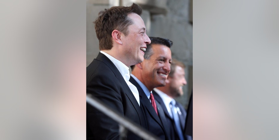 Tesla Motors CEO Elon Musk, left, and Nevada Gov. Brian Sandoval announce Nevada as the new site for a $5 billion car battery gigafactory, during a press conference at the Capitol in Carson City, Nev., on Thursday, Sept. 4, 2014. The move is expected to create 6,500 jobs. (AP Photo/Cathleen Allison)