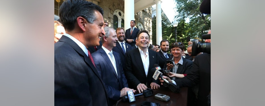 From left, Nevada Gov. Brian Sandoval, Steve Hill, executive director of the Governor's office of economic development, and Telsa Motors CEO Elon Musk answer questions following a news conference at the Capitol, in Carson City, Nev., on Thursday, Sept. 4, 2014. Nevada Gov. Brian Sandoval announced Thursday that Tesla Motors will build a massive battery factory in the state as long as legislators approve tax breaks and other incentives worth up to $1.3 billion over 20 years. (AP Photo/Cathleen Allison)