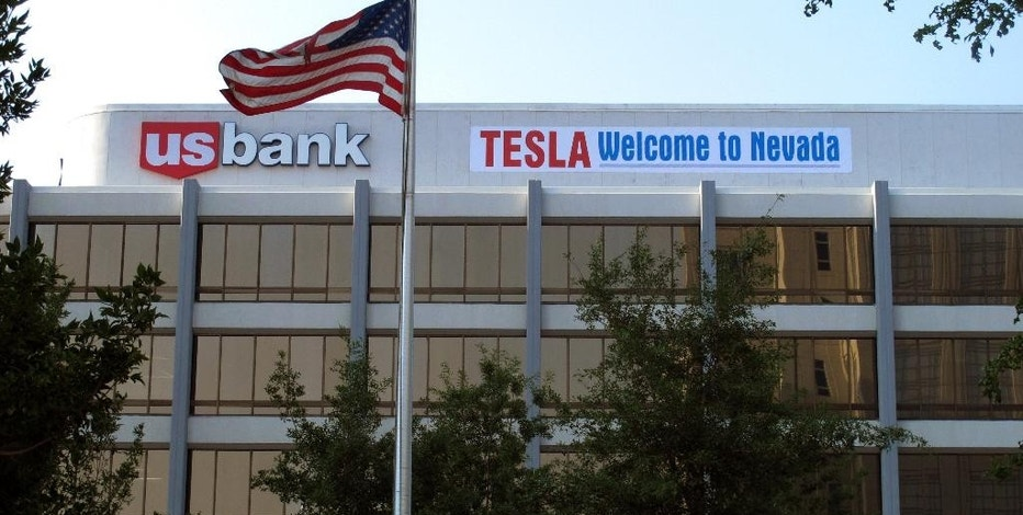 """A banner welcoming Tesla to Nevada is hung on the US Bank building just south of the downtown Reno casino district on Tuesday, Sept. 9, 2014,  in Renvo, Nev. State lawmakers planned to meet in a special legislative session in Carson City on Wednesday to consider a package of tax breaks and incentives worth up to $1.3 billion to seal a deal to bring the electric car maker's $5 billion lithium battery """"gigafactory'' to an industrial park in the state. (AP Photo/Scott Sonner)"""