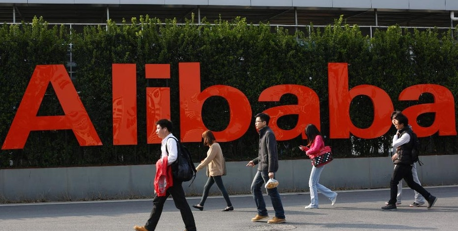 FILE - In this March 17, 2014 file photo, people walk past a company logo at the Alibaba Group headquarters in Hangzhou, in eastern China's Zhejiang province. Alibaba Group's U.S. stock offering is a wakeup call about an emerging wave of technology giants in China's state-dominated economy. Until now, Chinese companies that made a splash in global stock markets were state-owned banks and oil companies. But they are big by decree, not because they sell products customers want. By contrast, private sector tech champions such as Lenovo Group in personal computers and search engine Baidu Inc. survived bruising competition to rise to the top of their industries. (AP Photo/File)  CHINA OUT