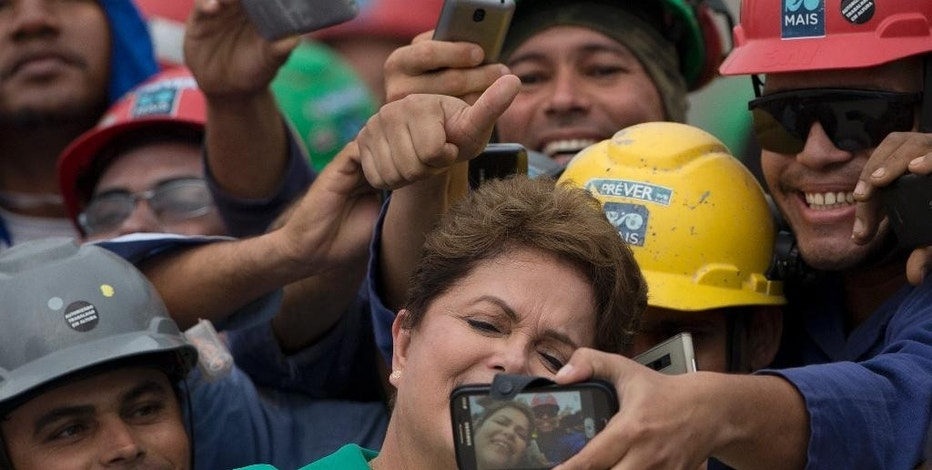 Brazil's President Dilma Rousseff, center, takes a selfie with workers during a visit to the Rio 2016 Olympic Park in Rio de Janeiro, Brazil, Tuesday, Sept.30, 2014. Chaired by Nawal El Moutawakel, the IOC Coordination Commission makes its seventh visit to Rio de Janeiro to monitor the preparation of the city for the 2016 Olympic and Paralympic Games. (AP Photo/Silvia Izquierdo)