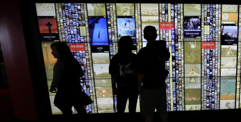 In this photo taken Sept. 19, 2014, visitors to the Space Needle in Seattle interact with a large touch-screen photo display wall that lets visitors see historical photos as well as photos shared by other visitors. The display as well as a new tablet and mobile phone app are adding to the allure of one of Seattle's top tourist destinations. (AP Photo/Ted S. Warren)