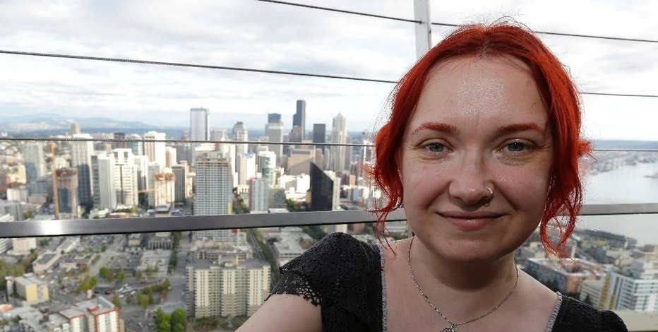 In this photo taken Sept. 19, 2014, Marie Schulz, of London, poses for a photo with her new tattoo featuring the  Seattle skyline, atop the the Space Needle in Seattle. A new Space Needle tablet and mobile phone app and other accompanying attractions are adding to the allure of one of Seattle's top tourist destinations. (AP Photo/Ted S. Warren)