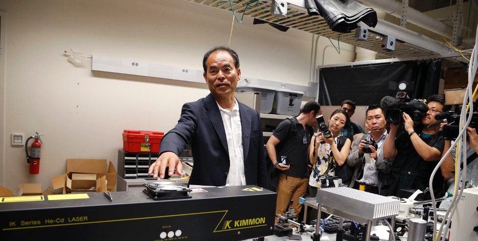 Japanese-born U.S. citizen Shuji Nakamura talks about a laser in a lab after winning the 2014 Nobel Prize for Physics, at the University of California Santa Barbara in Isla Vista, California October 7, 2014.  REUTERS/Lucy Nicholson