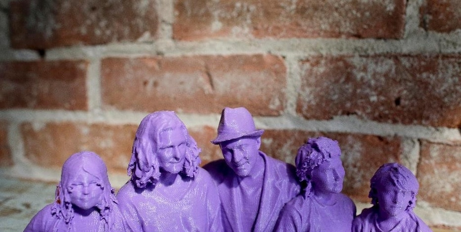 In this Aug. 14, 2014 photo, a plastic bust statue of Kevin Micelli, center, and his family, made by a 3-D scanner and printer, sits on a shelf inside Micelli's coffee shop in New York. Micelli purchased the 3-D scanning and printing services at the Cubo toy store next door to his shop. With the old studio portrait supplanted by the selfie, 3-D scanning services provide a new reason for people to go to a store and stand stock-still in front of a camera. (AP Photo/Julie Jacobson)