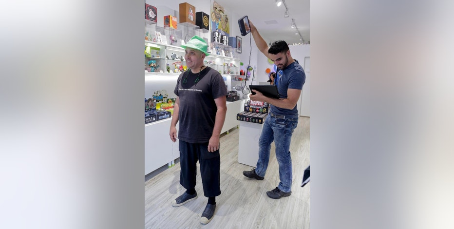 In this Aug. 14, 2014 photo, Victor De Los Angeles, left, owner of Cubo toy store, demonstrates a Sense 3D scanner on coffee shop owner Kevin Micelli at his store in New York. With the old studio portrait supplanted by the selfie, 3-D scanning services provide a new reason for people to go to a store and stand stock-still in front of a camera. (AP Photo/Julie Jacobson)