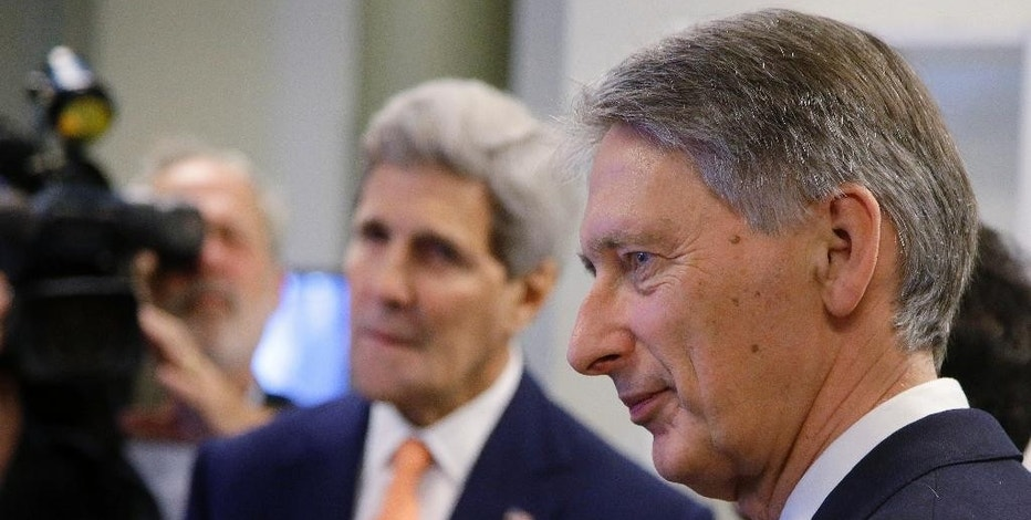 British Foreign Secretary Philip Hammond, right, and Secretary of State John Kerry tour the control room at the Wind Technology Testing Center, Thursday, Oct. 9, 2014, in Boston. (AP Photo/Stephan Savoia)