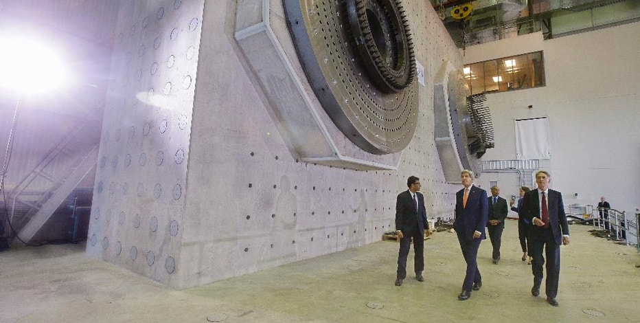 Secretary of State John Kerry, center, and British Foreign Secretary Philip Hammond, right, tour the Wind Technology Testing Center, Thursday, Oct. 9, 2014. in Boston. (AP Photo/Stephan Savoia)