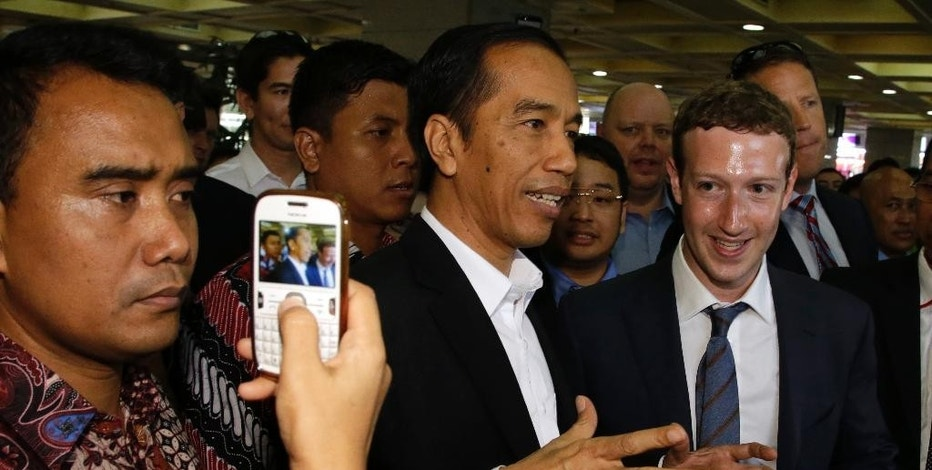 Indonesian President-elect Joko Widodo, center, speaks with Facebook CEO Mark Zuckerberg, right, during their visit to a market in Jakarta, Indonesia, Monday, Oct 13, 2014. Zuckerberg and Widodo discussed ways to take advantage of the online social networking service for beneficial of national development. (AP Photo/Achmad Ibrahim)