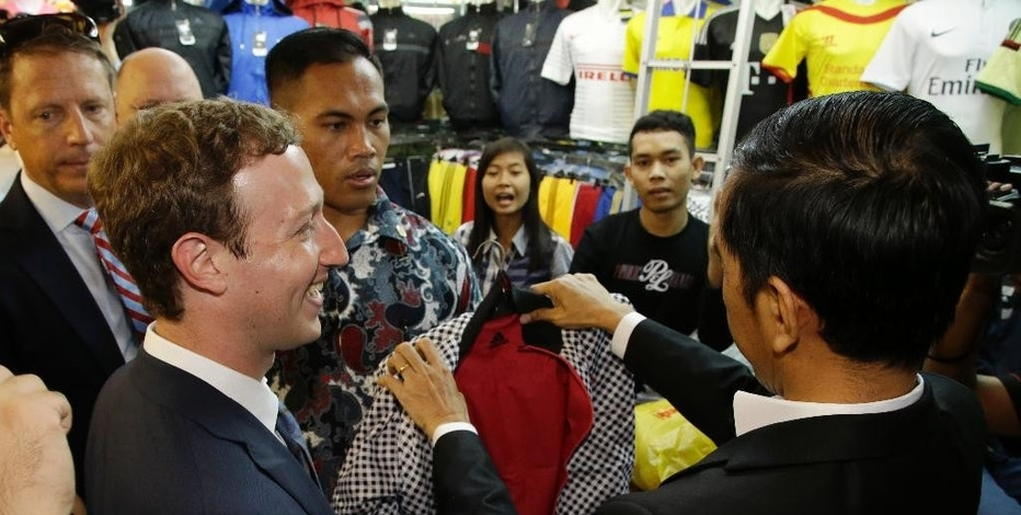 Facebook CEO Mark Zuckerberg, left, and Indonesian President-elect Joko Widodo, left, examines a cloth during a visit to a market in Jakarta, Indonesia, Monday, Oct. 13, 2014. Zuckerberg and Widodo discussed ways to take advantage of the online social networking service for beneficial of national development. (AP Photo/Achmad Ibrahim)